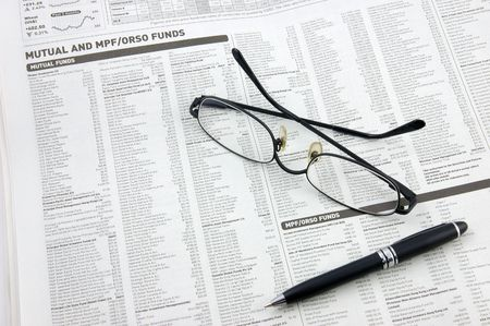 mutual: Glasses, pen over mutual funds data on newspaper