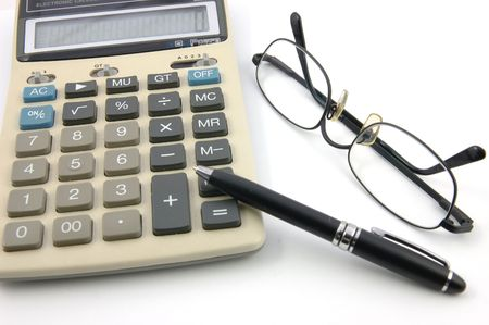 Lunettes, stylo et calculatrice dans le blanc disolement Banque d'images