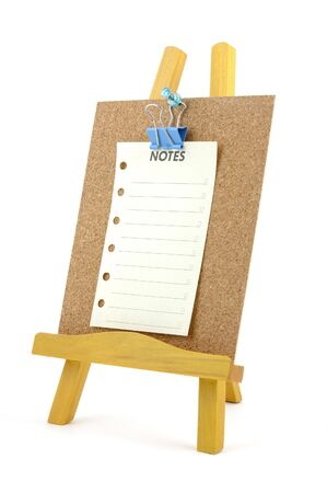 Pinned note on corkboard with wooden stand, isolated background photo