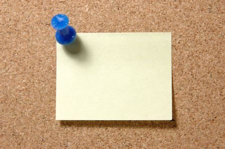 Yellow post-it note with blue pushpin on corkboard photo