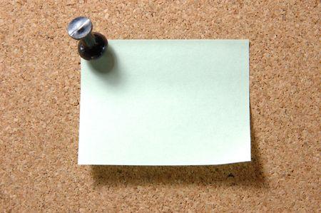 memorise: Green post-it note with black pushpin on corkboard Stock Photo
