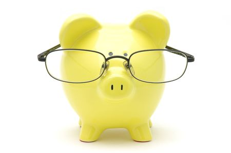 Yellow piggy bank with glasses in isolated white background photo