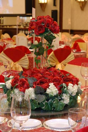 Wedding banquet table setting with a bouquet of red roses