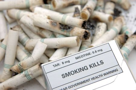 kills: Government warning message: Smoking Kills, in cigarette butts background Stock Photo