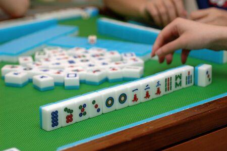 mahjong: People playing mahjong on a table Stock Photo