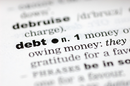 definition define: A close up of the word debt from a dictionary