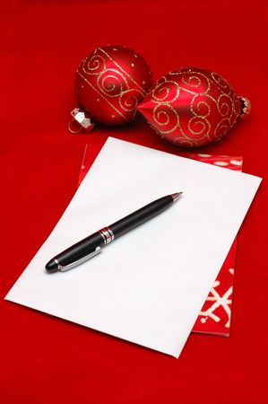 Empty christmas envelope with ornaments, over red background photo