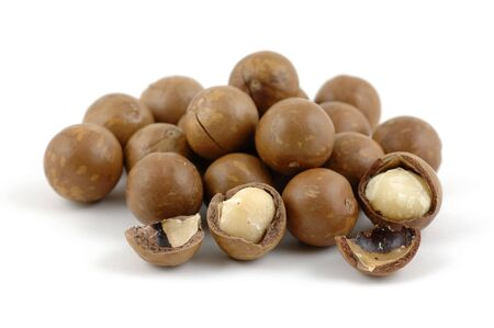shelled: Shelled and unshelled macadamia nuts in isolated white background