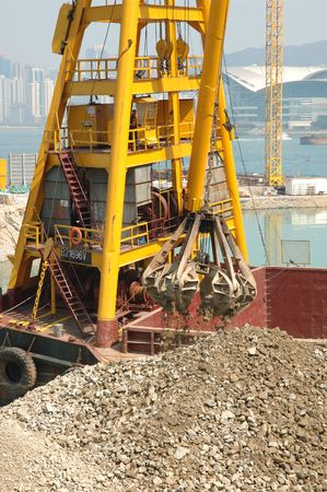 reclamation: Construction ship moving stones in a reclamation Stock Photo