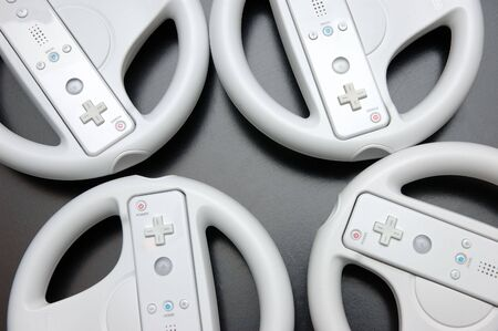 wii: Video game racing wheel consoles over black background