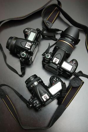 digicam: Three DSLR cameras over black background