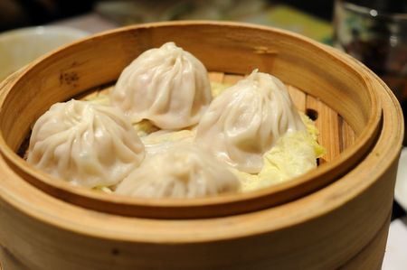 Close up of Shanghai soup dumplings in bamboo steamer