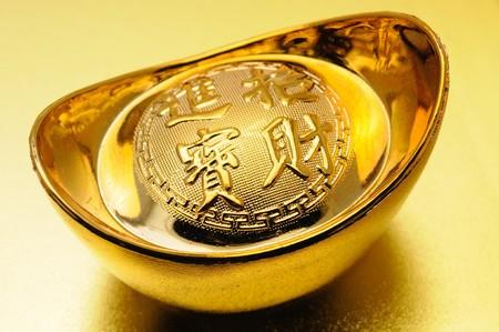 lingotto: Primo piano cinese di lingotto d'oro su sfondo dorato