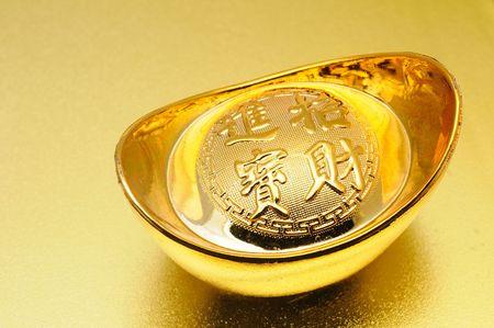lingotto: Primo piano di lingotto d'oro cinese su sfondo dorato