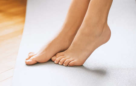 Side close up view of unrecognizable woman feet legs, barefoot standing indoors, enjoying warm wooden heated floor.