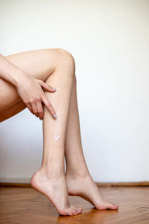 Side close up view of unrecognizable woman legs lstanding indoors.