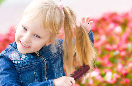 Pretty blond girl combing her hair photo