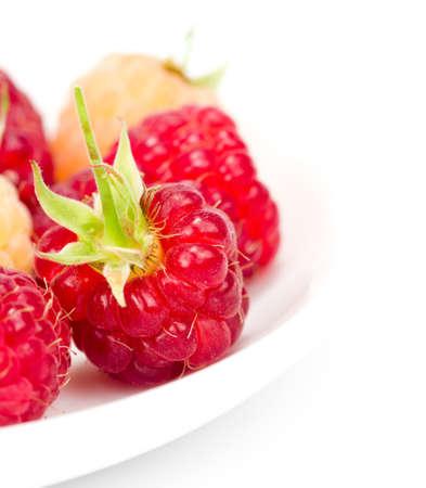 plateful: plateful of fresh raspberries on white  Stock Photo
