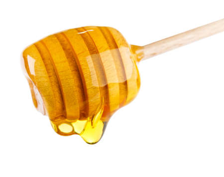 dripped: Honey dripping from a honey dipper. Isolated on white background