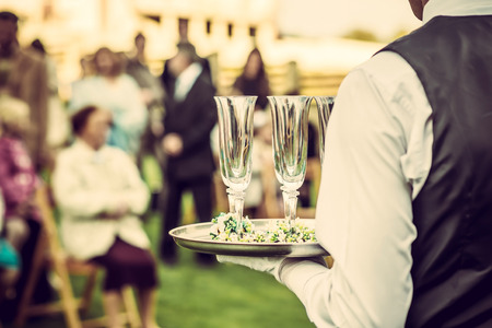 Waiter with glasses on the tray at wedding ceremony, waiting for champagne 스톡 콘텐츠