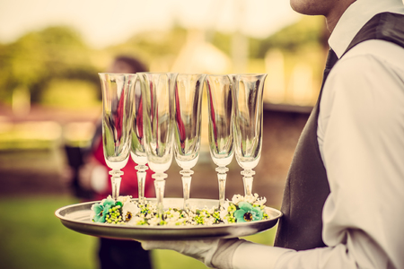 banquet: Waiter with glasses on the tray at wedding ceremony, waiting for champagne Stock Photo
