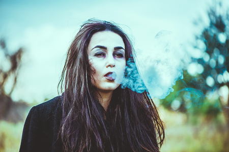 ghost woman: Girl with scary face painting smoking