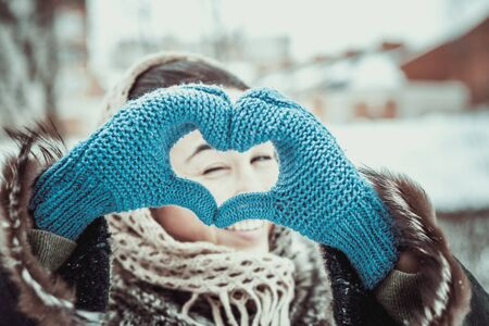 shaped hands: Pretty girl with heart shaped hands is the gloves outdoor Stock Photo