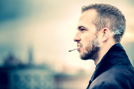 feeling happy: Man with beard on the top of the high building with cityscape on background