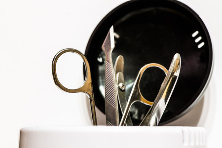 grooming product: Manicure accessories in tool sterilizer isolated on white background Stock Photo
