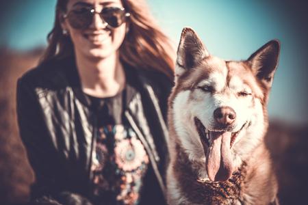 ragazza innamorata: Il cane husky all'aperto con la ragazza felice dietro