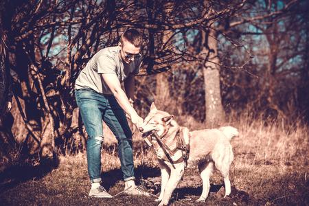 puppy love: Hombres con su perro Husky jugando en el parque Foto de archivo