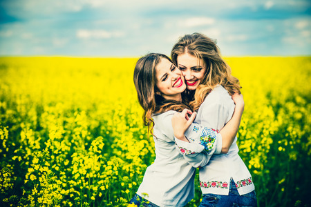 women friendship: Two pretty girls in the yellow field in embroidery shrts