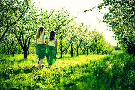 pies bonitos: Dos muchachas bonitas que recorren en el verde jard�n con �rboles de manzana Foto de archivo