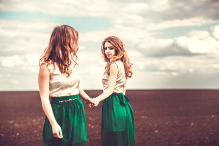 girls holding hands: Two pretty girls holding hands in the brown field