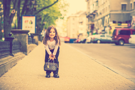 jeans girl: Pretty little girl walking on the city street Stock Photo
