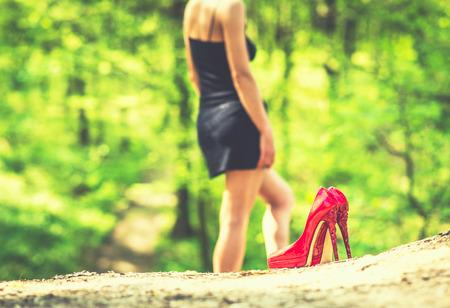 pies sexis: chica morena descalzo al aire libre con tacones rojos