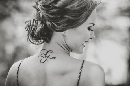 short: Portrait of young brunette girl with tattoo on the neck Stock Photo
