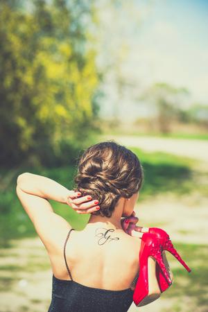 Barefoot brunette girl outdoor with red high heels in her hands