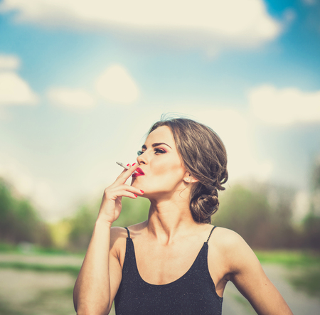 Pretty brunette woman smoking sigarette outdoor Stock Photo