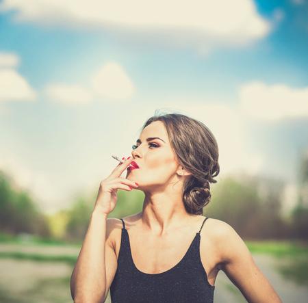 Pretty brunette woman smoking sigarette outdoor Standard-Bild
