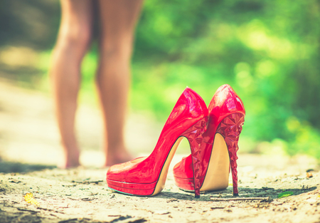 without legs: Red high heel shoes on the ground with barefoot girl on background