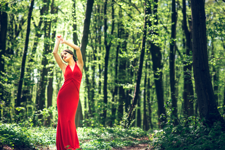 Pretty woman in long red dress walking in the forest