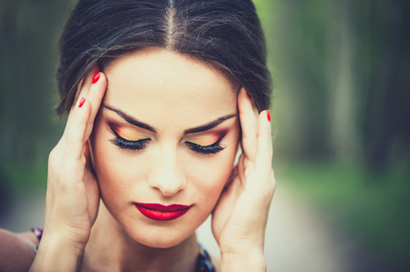 headache: Pretty brunette girl touch her head, showing headache