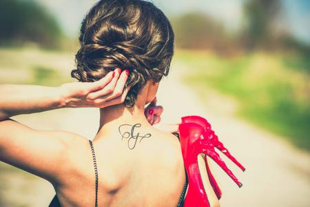 tatouage sexy: Pieds nus fille brune en plein air avec des talons hauts rouges dans ses mains