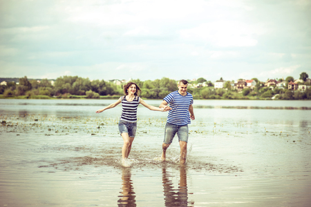 caucasian water drops: Lovely couple outdoor, running on the lake