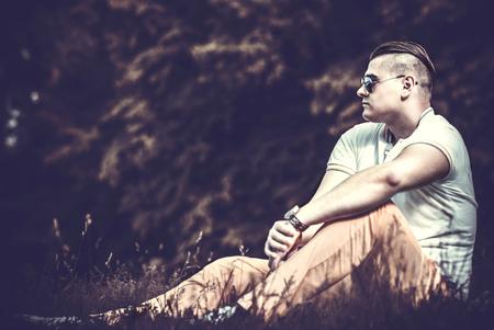 modelos hombres: Hombre brutal que se sienta en el suelo al aire libre en gafas de sol Foto de archivo