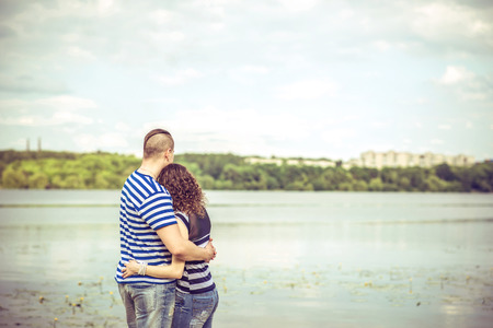 hombres besandose: Lovely couple outdoor with lake on background Foto de archivo