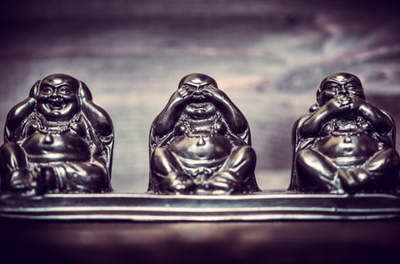 philosophy: Three figures of Buddha philosophy on wooden background