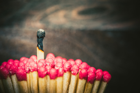 One burned match standing out from the crowd of mathes