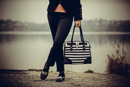 Girl in black and white shoes with black and white bag in her hands outdoor Standard-Bild